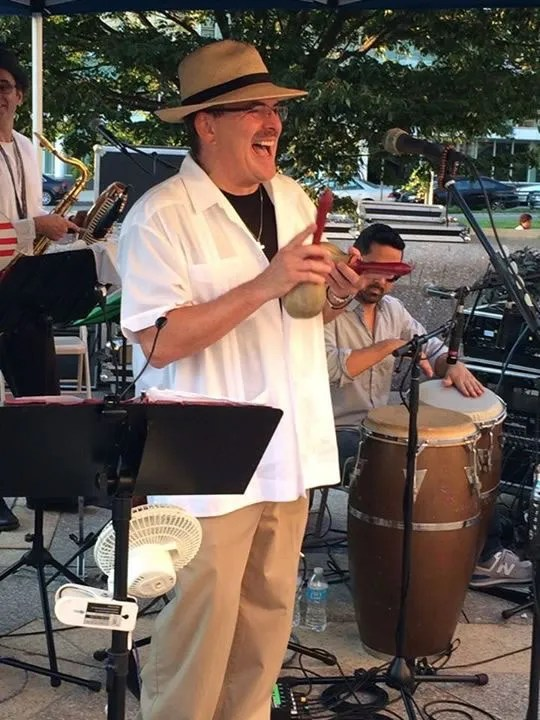 JuanMa-playing-maracas-singing-smiling-BPL-outdoor-music-series