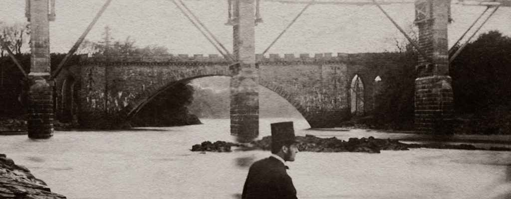 grayscale photo man wearing a top hat and suit sitting by the river near a bridge