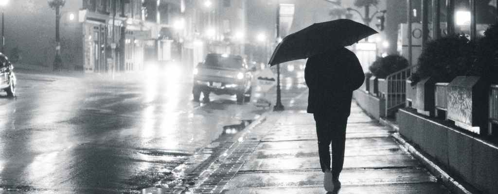 man with umbrella on glowing night street