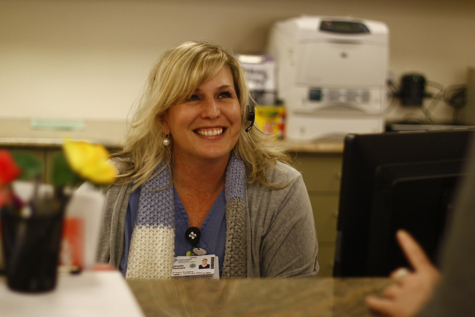 Janelle, a Job Link client, behind the desk at her new Administrative Medical Assistant job