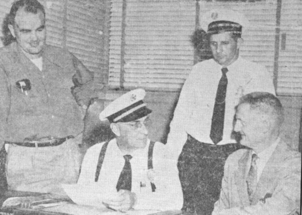 Four men in an office in black and white newsprint