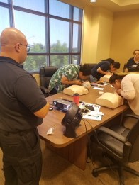 CPR trainees breathing into the mouths of CPR dummies