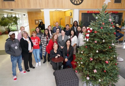 BC staff smiles by Christmas Tree