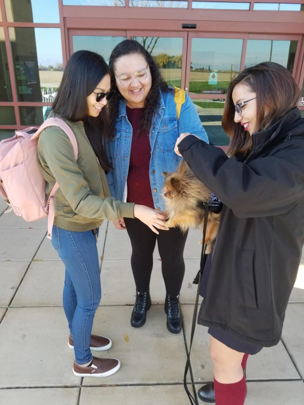 Students holding dog