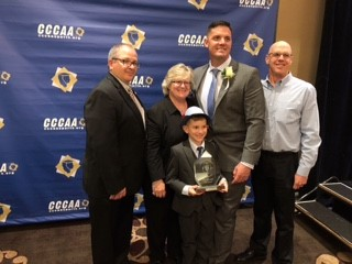 Jeremy poses with Keith Ford, Assistant director of athletics, Sandi Taylor, director of athletics, his son and another man.