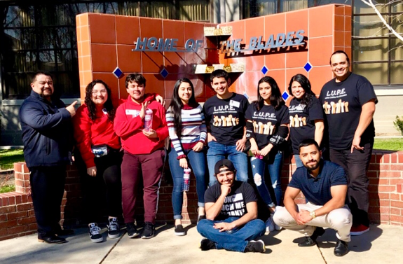 "Lupe students pose in front of the ""Home of the Blades"" sign."