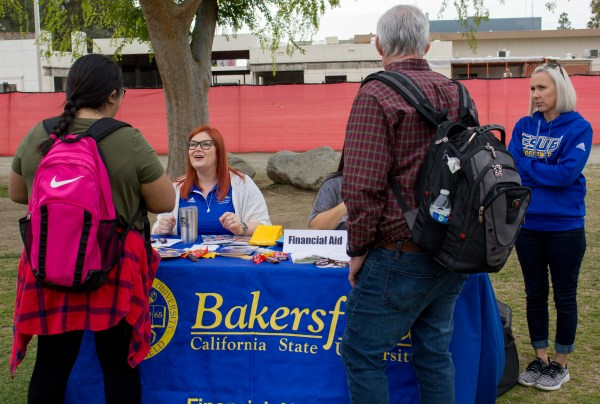 A CSUB staff member at the Financial Aid table talks to students.