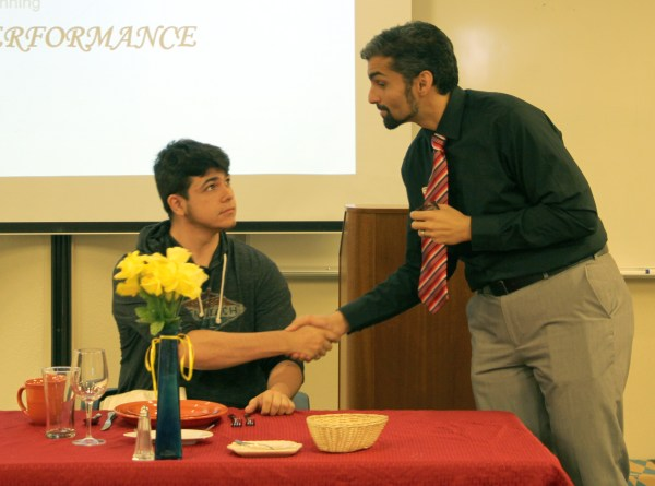 Nicky Damania shaking hands with male student