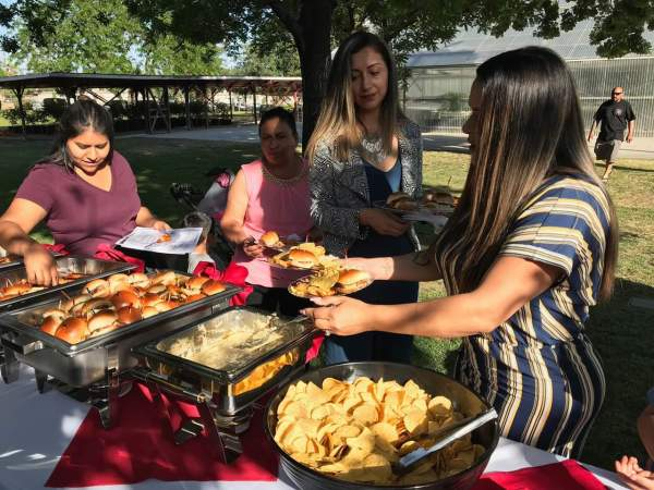 Graduates serving themselves hamburgers and sides at the buffet.