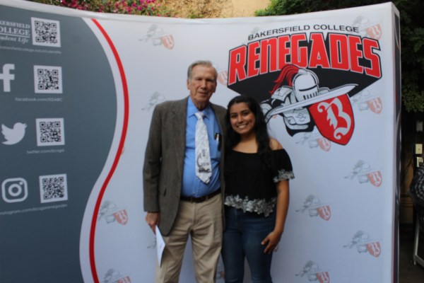 Male faculty and female student in front of Renegade logo backdrop.
