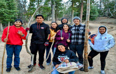 8 students pose and smile among the trees.