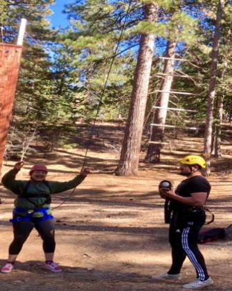 One student with helmet watches as another is in zip line harness.