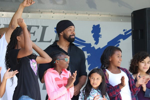 DJ and students clap and cheer on stage.