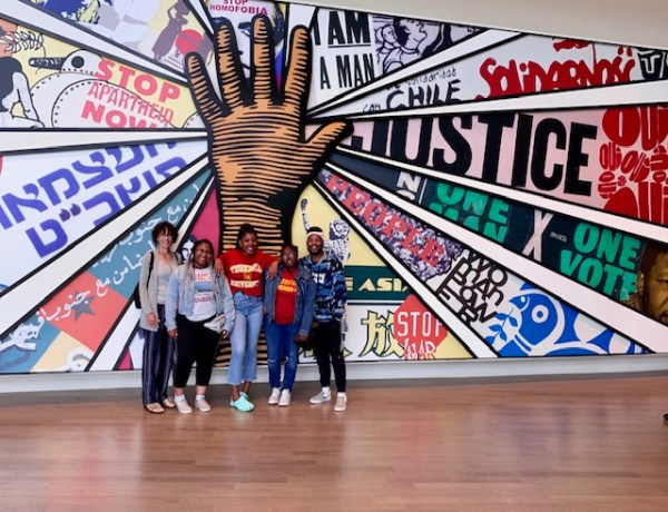 Tour group with a mural of a hand with snippets: stop apartheid, I am a man, justice, one vote.