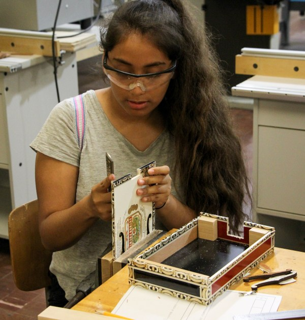 Student wearing safety goggles working on constructing guitar.