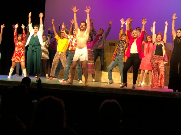 Actors perform song with hands in air.