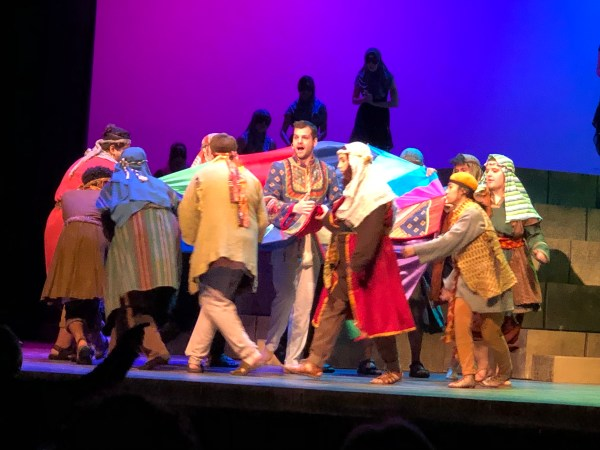 Actors sing and dance around a quilt.