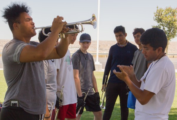 Bugle player plays while another student claps and others look on.