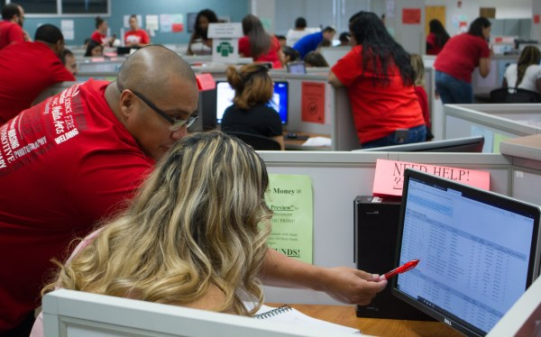 Staff pointing out how to enroll on a computer.
