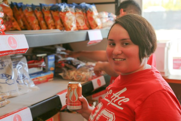 Staff placing a can of soda on the shelf.