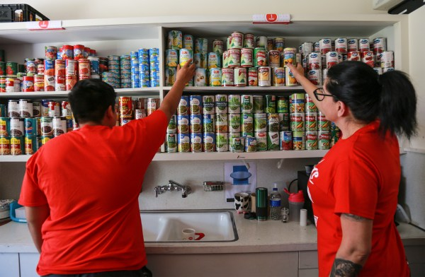 Pantry workers reach for cans on well stocked shelves.