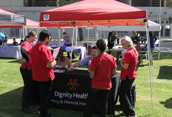 Nursing students gathered around the Dignity Health rep.