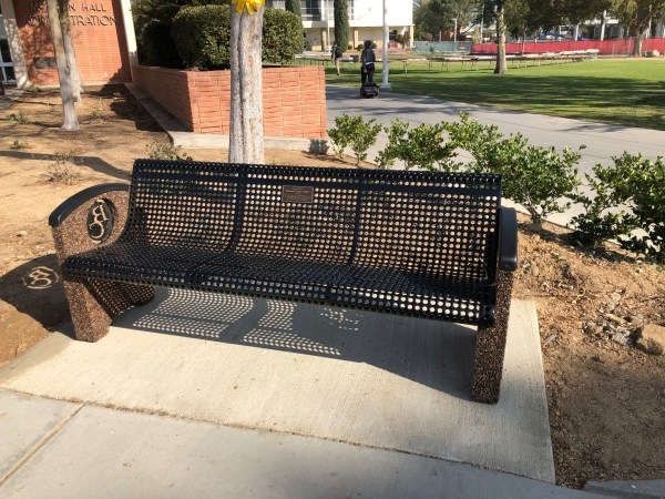 Metal bench with pebbled sides and BC emblems.