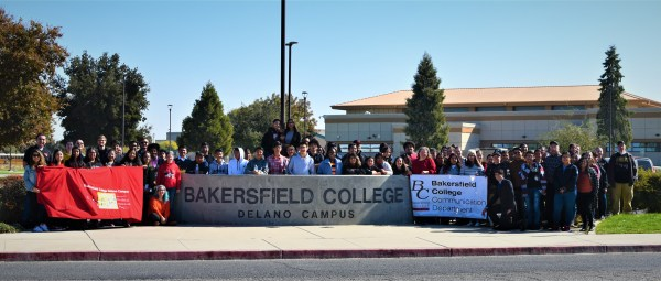 Large crowd behind the Bakersfield College Delano Campus sign.