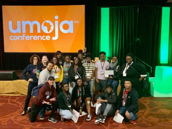 BC Students with Paula in front of the Umoja Conference sign.