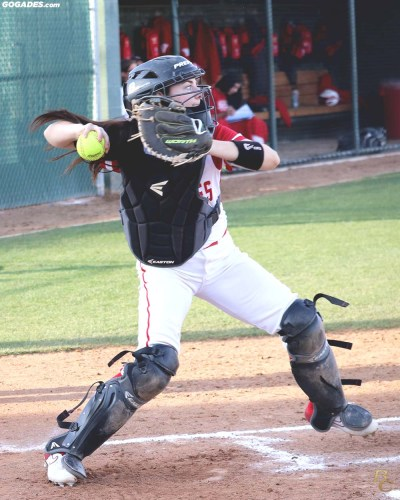 Female catcher throwing softball.