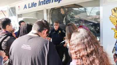 "A BPD officer speaks to students at a mock press conference in front of the ""A Life Interrupted"" trailer."