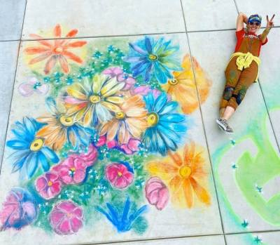 Laying next to chalk drawing of flowers.