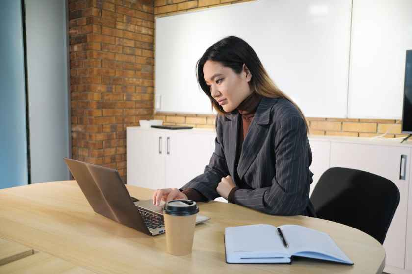 asian businesswoman typing on laptop at table in office