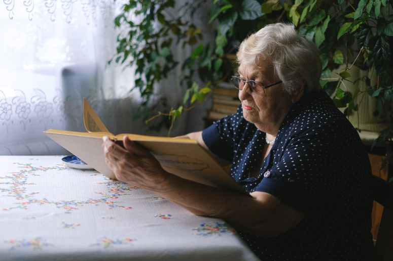 senior woman reading book in room