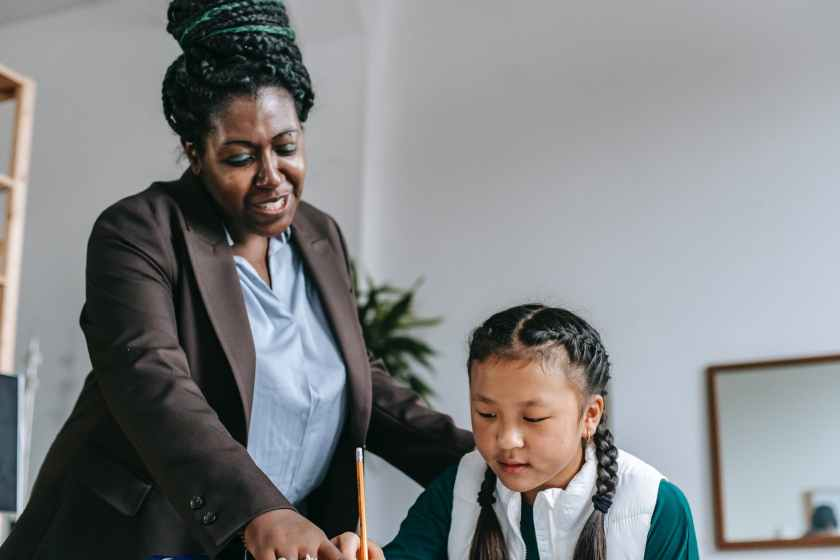 black female tutor explaining question to asian girl in classroom