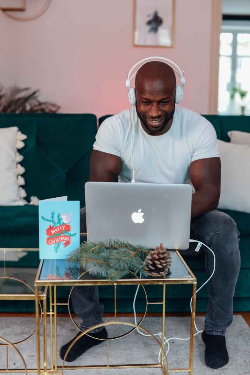 man in white crew neck t shirt sitting on a chair using macbook