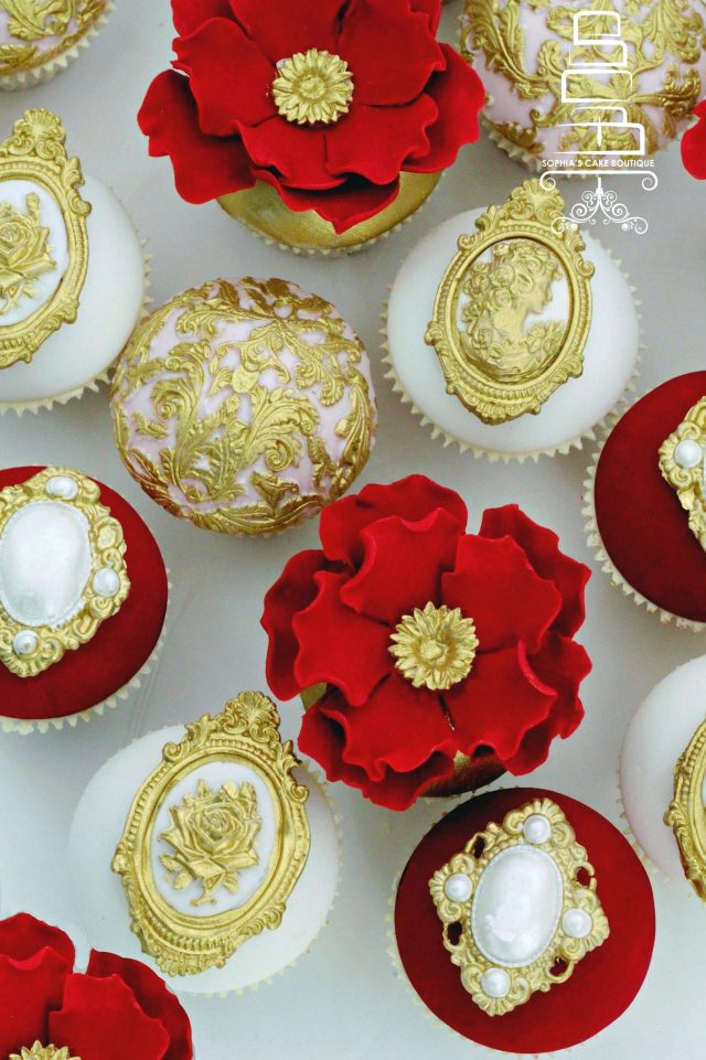 red, gold and ivory cupcakes embellished with fondant flowers and brooches