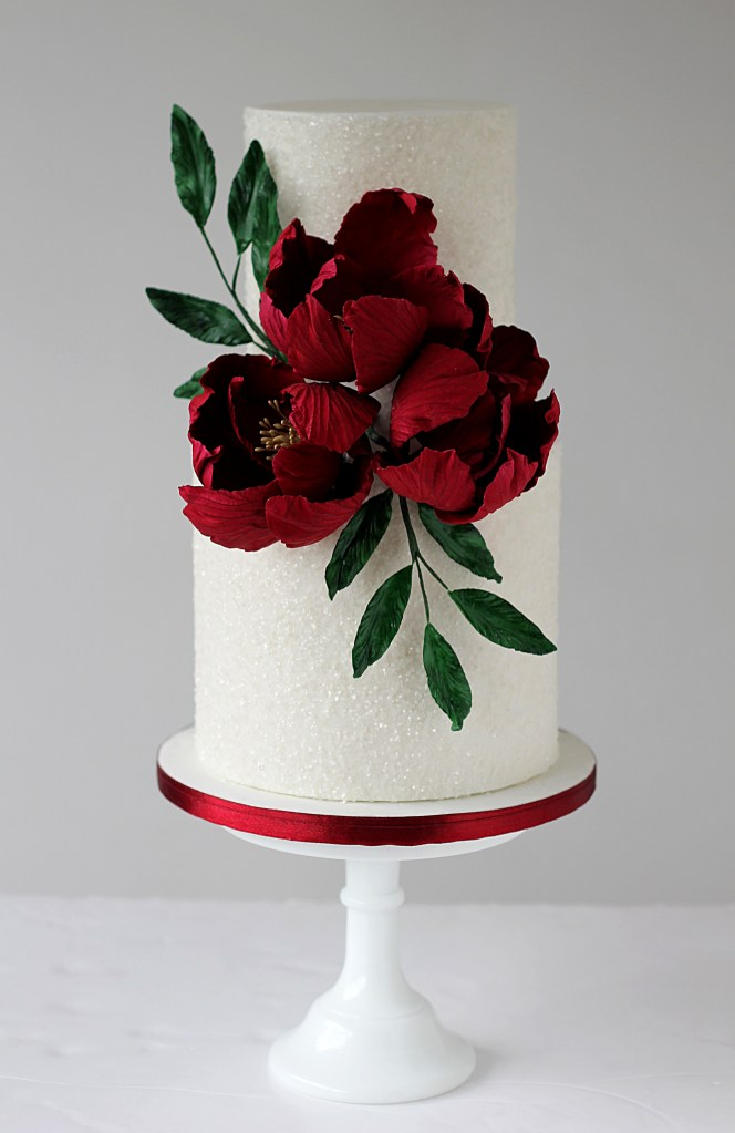 White sparkly two tier wedding cake with deep red sugar flowers and green foliage