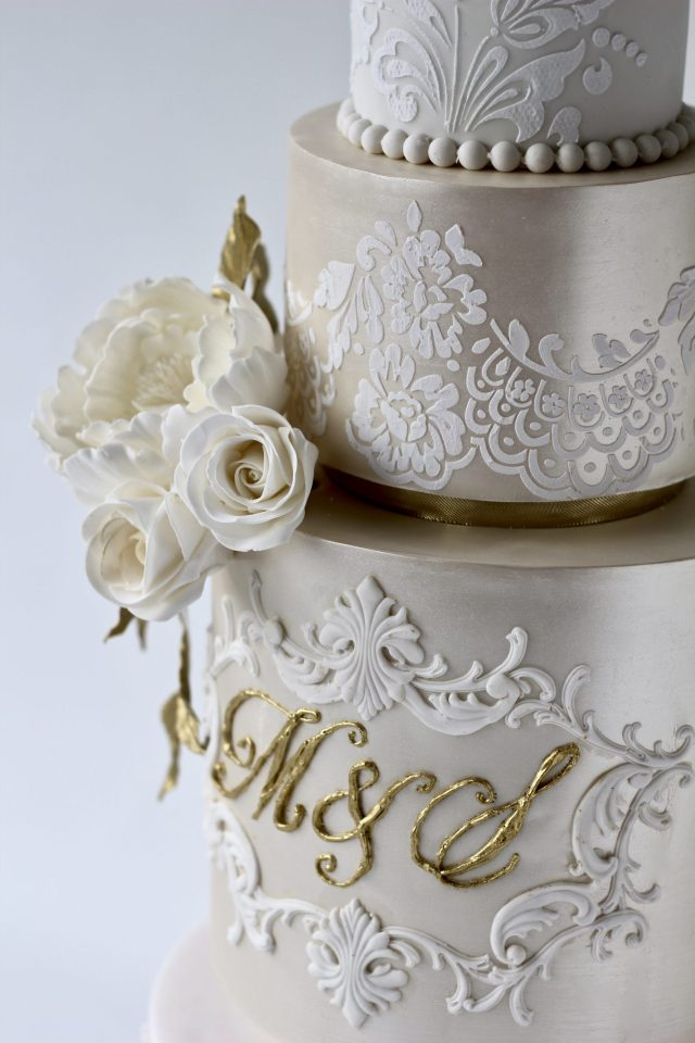 four tier ivory and champagne coloured wedding cake with lace stencil pattern, ivory flowers and a Champagne shimmer