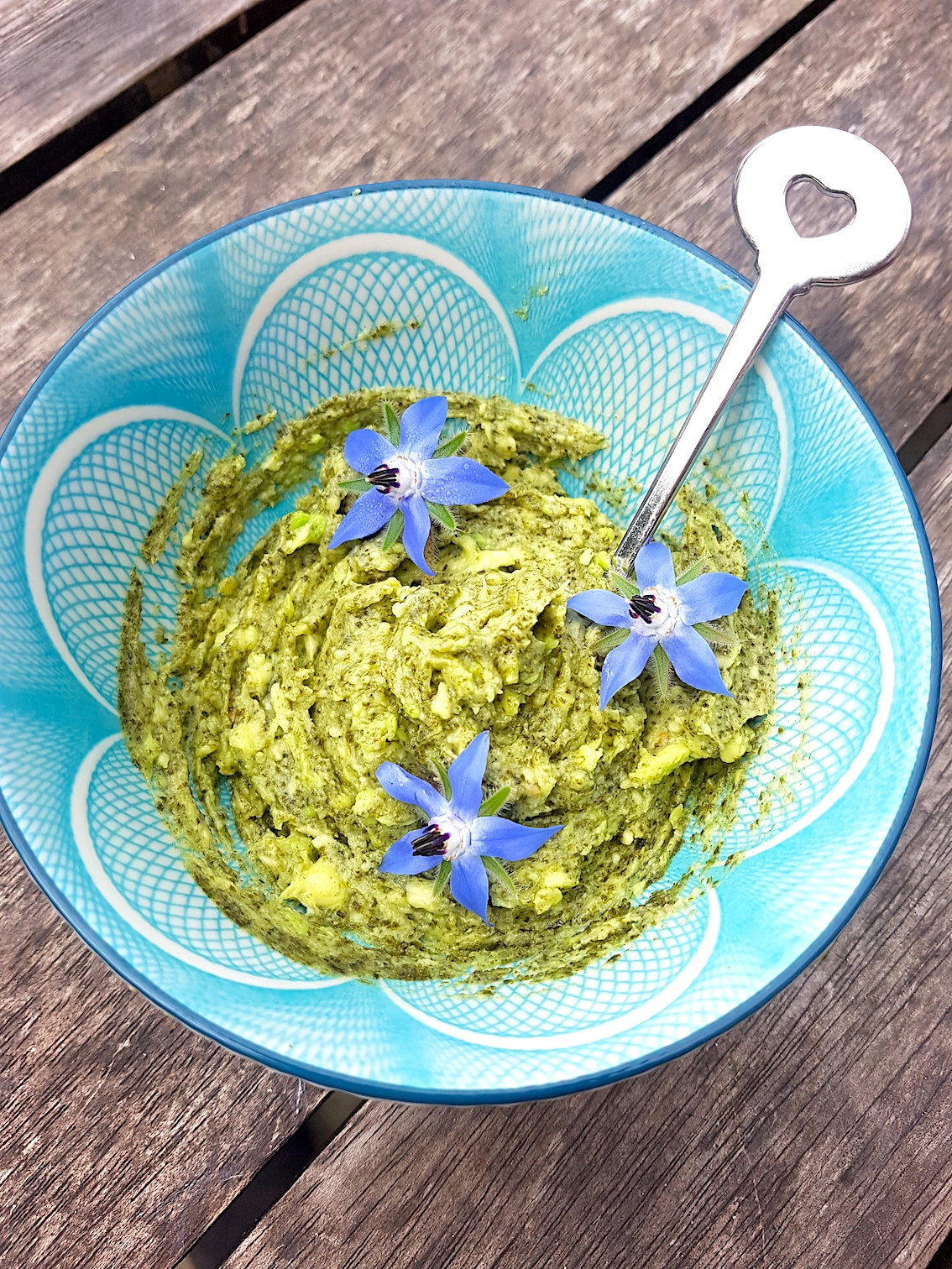 Avocado and kelp face mask in a pretty blue bowl with decorative edible flowers