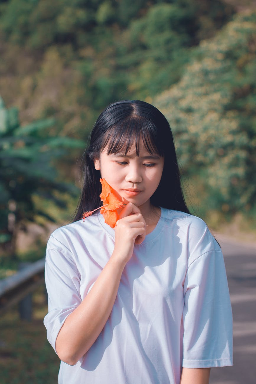 woman holding orange hibiscus flower