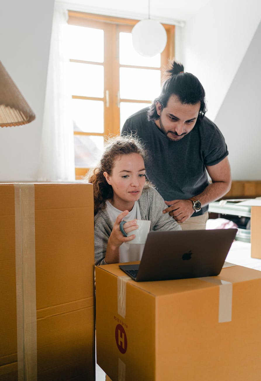 multiracial couple watching laptop while drinking coffee in new apartment