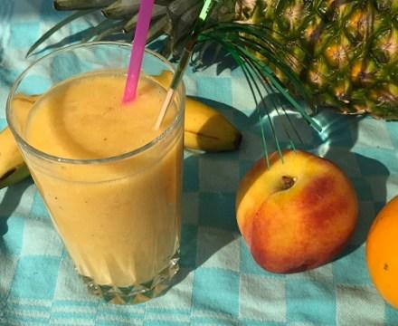 Tropische smoothie met ananas, banaan, perzik en sinaasappel
