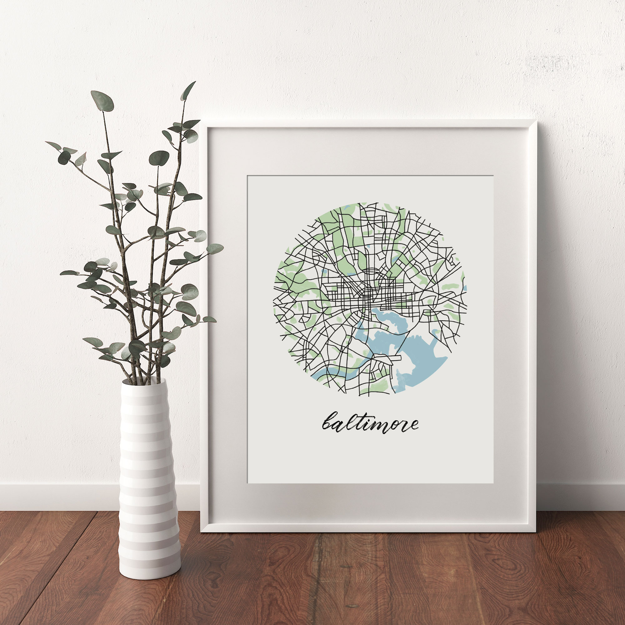 Baltimore Map print framed and leaning on white wall next to dried leaves in a vase