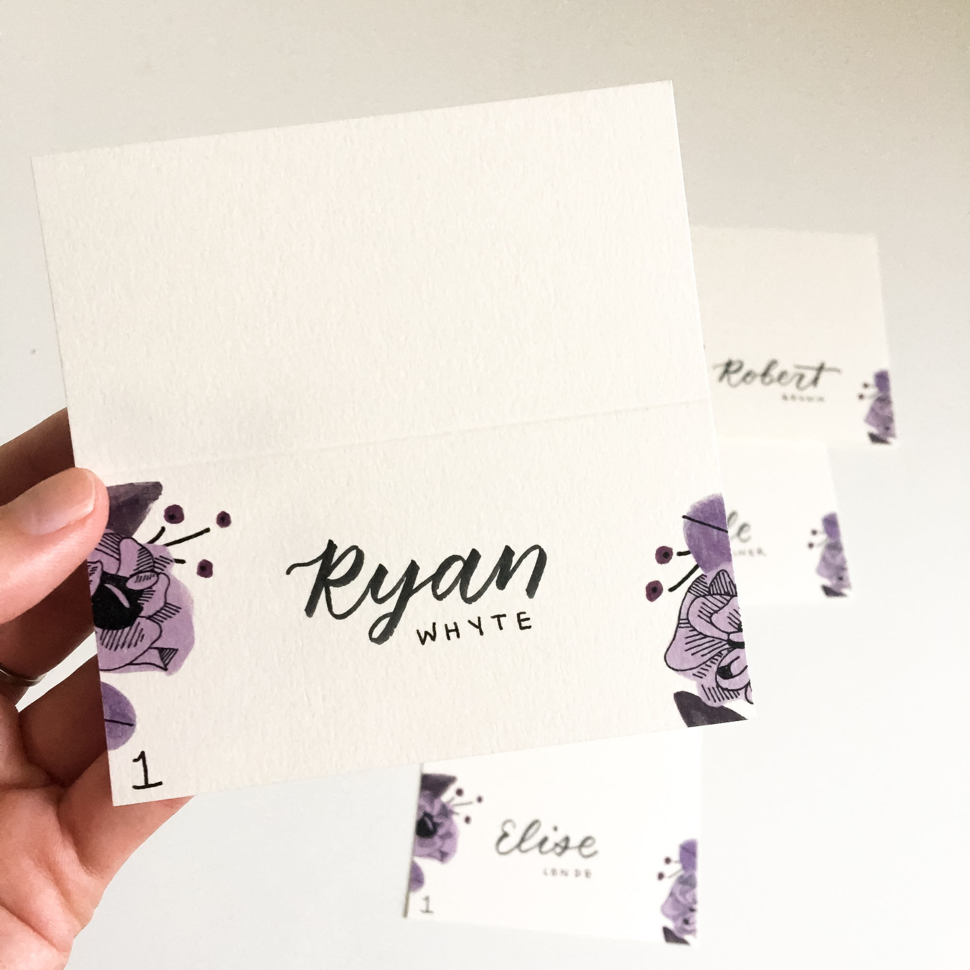 Hand holding a place card for Ryan Whyte, table 1