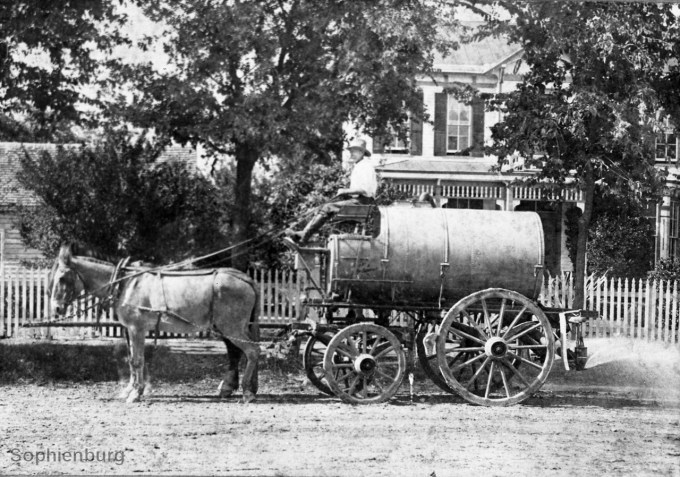 Mule-drawn sprinkler wagon 1905. Bare-foot children loved the coming of the wagon on their street. They would run behind the sprinkler to wet their feet and legs in the spray. (S588-051)