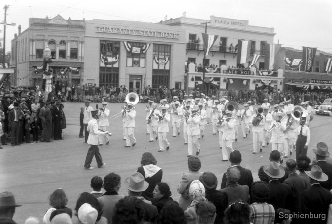 Spectators at the corner of West San Antonio Street and Main Plaza watch as a military band passes during the Centennial Parade in May 1946. (S465080-29)