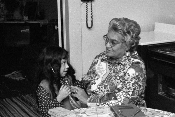 Photo Caption: Lina Chapa Delgado helping her granddaughter Michelle Ortiz listen to her heartbeat in January 1973. On the table are instruments given to Mrs. Delgado by Dr. Hylmar Karbach, Sr., a book on obstetrics from Dr. Frederick Casto and records of some of her 1,600+ deliveries. (New Braunfels Herald negative collection, Feb 1, 1973)