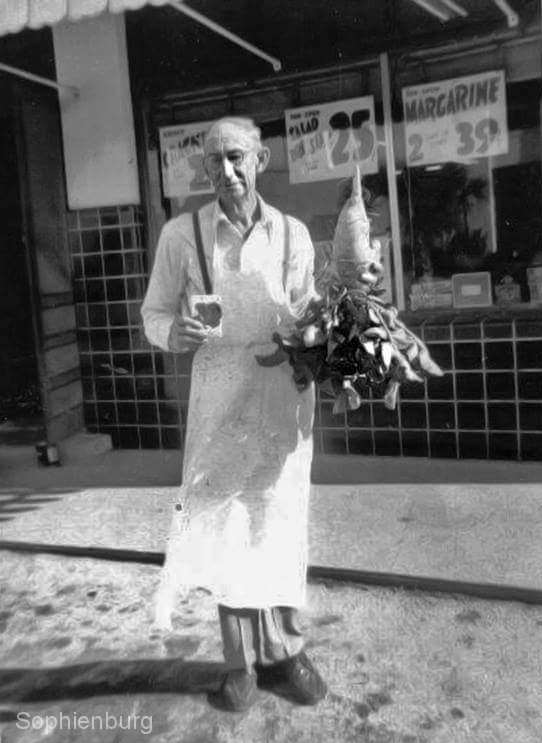 Photo: L.A. Pittman in front of Pittman's Red & White Store with a radish he grew with seeds purchased from his store.