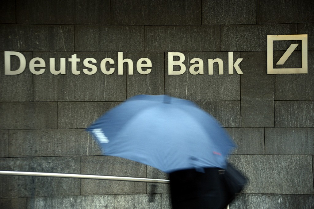 FRANKFURT AM MAIN, GERMANY - JANUARY 29: A woman with a umbrella passes a logo of Deutsche Bank on January 29, 2013 in Frankfurt am Main, Germany. The annual results press conference for 2012 takes place on Thursday, January 31, 2013. (Photo by Thomas Lohnes/Getty Images)